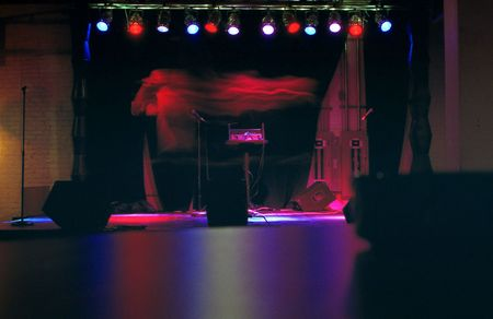 Long exposure of hip hop artist singing on stage.  Ghost like appearance.