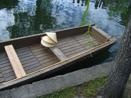 An empty boat with three straw hats waiting in a canal in Japan Stock Photo