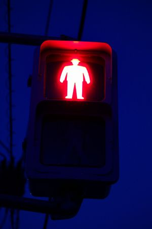 Pedestrian traffic signal red man glowing in the blue night Stock Photo