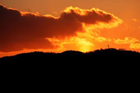 Orange sunset in mountains of Japan shining on clouds