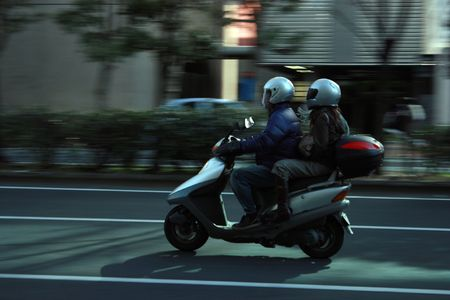 Couple riding moped in the city Stock Photo