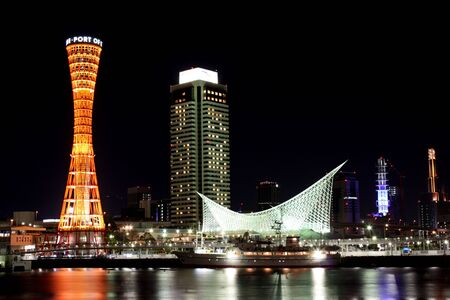 Kobe Port Tower and buildings at night across harbor