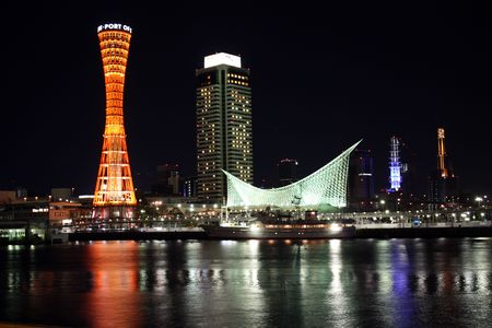 Kobe Port Tower and buildings at night from across harbor