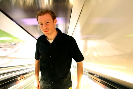 Man in 20s looking apprehensive, ascending an escalator away from the light.