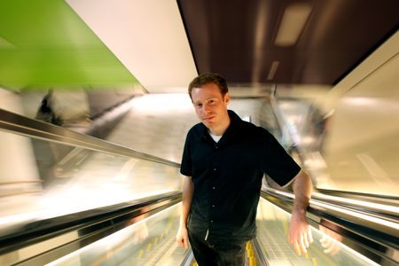 Happy man in 20s ascending an escalator with people blurring by. Stock Photo