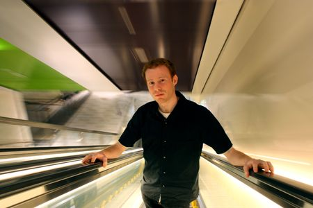 Man in 20s ascending an escalator, ambiguously apprehensive or serene.
