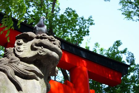 Pigeon sitting on lion statue at Shinto shrine entrance gate