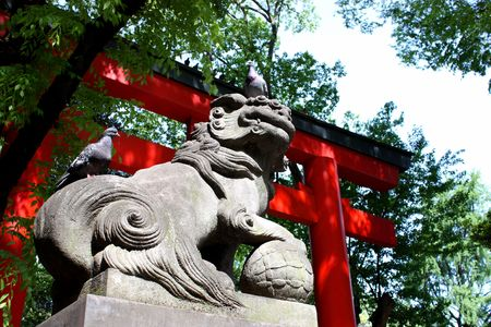 Two pigeons sitting on lion statue at Shinto shrine entrance gate