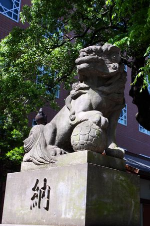 Pigeon sitting on statue of lion at Tokyo shrine entrance Stock Photo