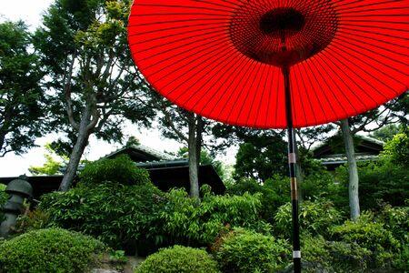 Red parasol in a Japanese tea house garden.