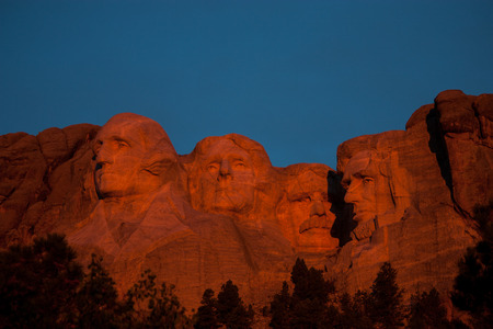 Sunrise over Mount Rushmore National Monument in the Black Hills of South Dakota.  Presidents are bathed in morning orange glow.
