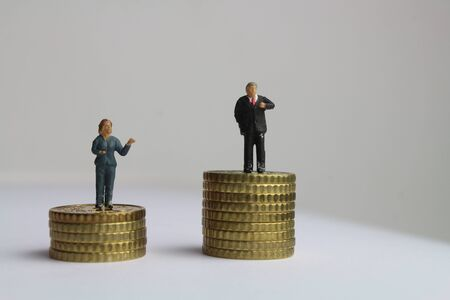 A stack of coins with figures of a businesswoman and a businessman symbolize the unequal payment