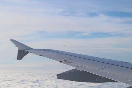 View from an airplane window of the wing with clouds and sky in the background