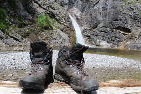 Mountain boots on a log with a waterfall in the background