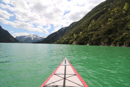 Top of a kayak in a lake with turquoise water and mountains in the background