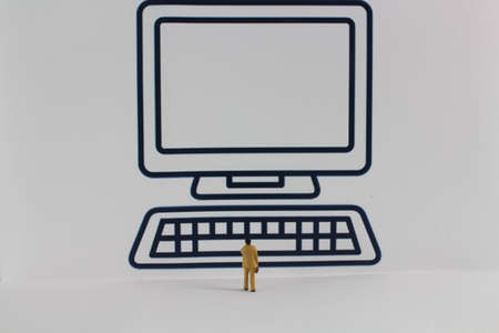small figure stands in front of a very large figure of a computer