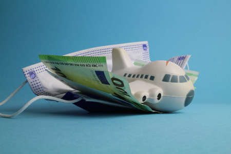 small plane with face mask and money stands for cancellation costs