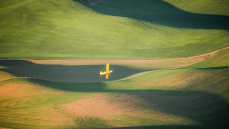 Crop Duster making a turn over a wheat field in The Palouse at sunrise 写真素材 - 103012325