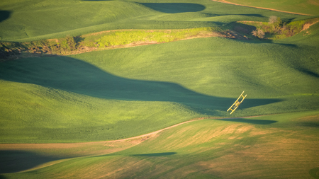 Crop Duster making a turn over a wheat field in The Palouse at sunrise 写真素材 - 103046108