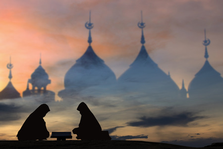 recite: Muslim girls read the Book Quran plea Middle East peace silhouettes background blur mosque.silhouettes Muslim woman praying reading the Quran,The believers in the Quran