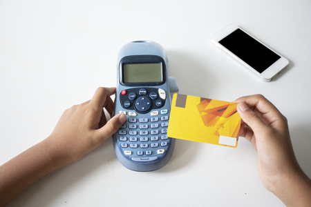 Een creditcard vasthouden en de beveiligingscode invoeren met behulp van een laptop, online betalingsapp-smartphone in coffeeshop, concept: zakelijke banktransacties met 5G-technologie via internetgegevens Stockfoto