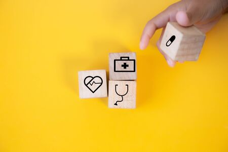 Children hands holding wood cube with a medical symbol,Concept: Health insurance family covid-2019 epidemic,management protect healthcare to a virus,care service doctor treatment for hospital Фото со стока