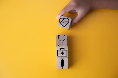Children hands holding wood cube with a medical symbol,Concept: Health insurance family covid-2019 epidemic,management protect healthcare to a virus,care service doctor treatment for hospital