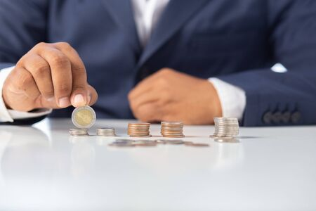 business man hand holding a coin in a glass bottle, Concept: saving  coin family money for home dreams,symbol growing  investment success wealth to  benefit, business growth  banking for  cash