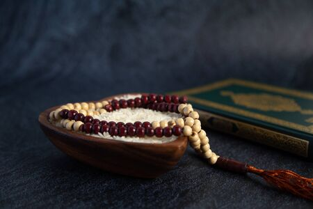 ZAKAT donation for Muslim according to religious principles during the Ramadan month, concept: rice grain in bow and rosary on black background