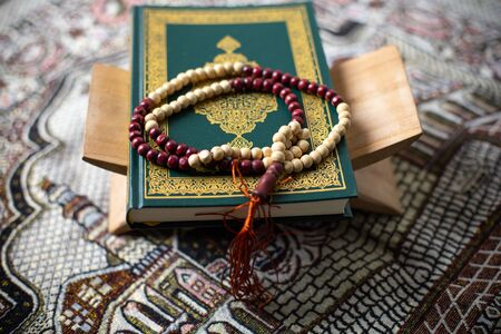 Quran and rosary laying on a wood background brown carpet in the mosque to read the prayer, In the month of Ramadan Muslim religion Islamic worshiping god faith and learn koran