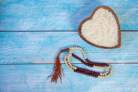 ZAKAT donation for Muslim according to religious principles during the Ramadan month, concept: rice grain in bow and rosary on wood