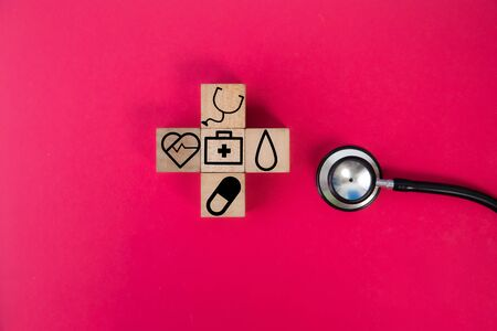 wood cube with a medical symbol  angle Flat lay,Concept: Health insurance family covid-2019 epidemic,management protect healthcare to a virus,care service doctor treatment for hospital Standard-Bild