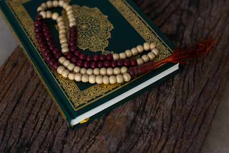 Quran - holy book of Muslims religion, Concept: open book holy prayers for god,Friday In the month of Ramadan  religion Islamic worshiping faith and learn koran and rosary put on wooden  boards