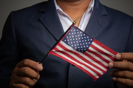 Businessman in a suit holding USA flag back background,