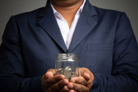 Businessman hand with putting money coins in the officeconcept: Saving money wealth and financial Personal, finance management  loan for a home, diagram chart earnings to plan profit Standard-Bild