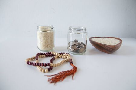 ZAKAT donation for Muslim according to religious principles during the Ramadan month, concept: rice grain in bow and rosary on a white table Standard-Bild