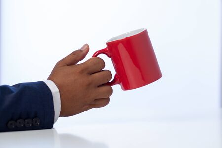 Businessman holding a coffee cup on the white table at the officeConcept: planning meeting working professional,beverage cafe breakfast for working, looking space to a morning lifestyleworkplace