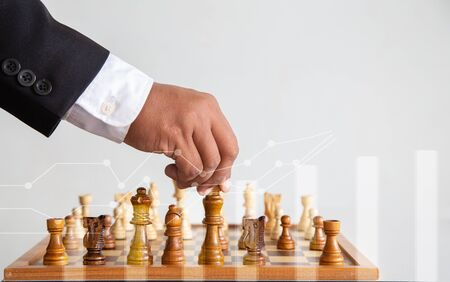 Businessman  hand moving of playing chess,  concept: leadership symbol confident new strategy plan for win and success, sports game  thinking battle planning object achievement queen for successful Standard-Bild