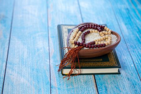 ZAKAT donation for Muslim according to religious principles during the Ramadan month, concept: rice grain in bow and rosary on wood Standard-Bild
