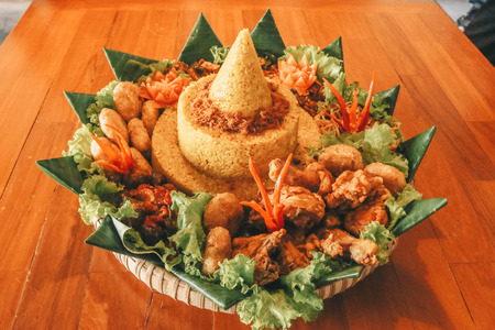 Traditional Indonesian Cuisine Nasi Tumpeng for Celebration. Tumpeng is a cone-shaped rice dish like mountain with meats usually eat as breakfast or lunch isolated on wooden background.