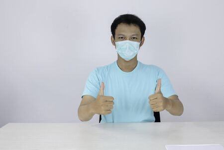 Young Asian Man wear medical mask is give ok hand sign with confident gestures. Indonesian man wearing blue shirt.
