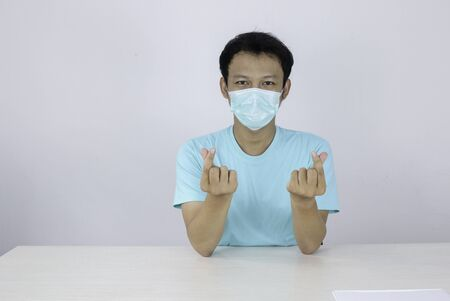 Young Asian Man wearing mask for protection from disease showing love korea sign with isolated white background. Coronavirus concept. Indonesian man wearing blue shirt. 免版税图像