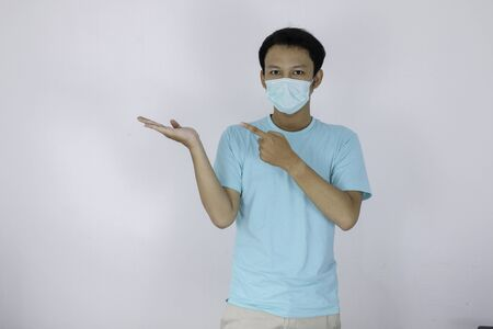 Happy face of young Asian man wear medical mask and blue with hand point on empty space.