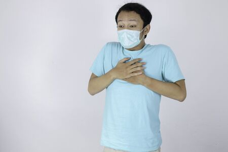 Young asian man wearing medical mask is suffering from severe headache, pressing fingers to temples, closing eyes to relieve pain with helpless face expression. Stok Fotoğraf