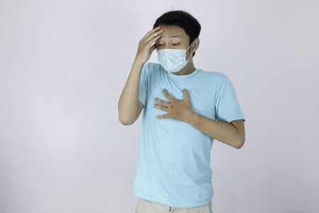 Sick Young Asian Man using medical mask is flu and headache with hand touch chest and forehead. Illness, Corona Virus, influenza, pain concept.