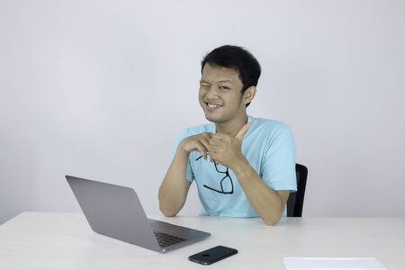 Young handsome asian man showing thumb up while working with laptop. Indonesian man wearing blue shirt.