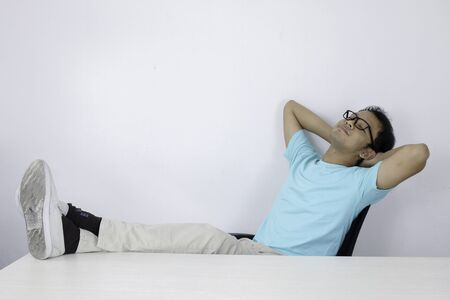 Calm smiling Young Asian Man relaxing at comfortable office chair hands behind head, happy man resting in office satisfied after work done, enjoying break with eyes closed, peace of mind, no stress