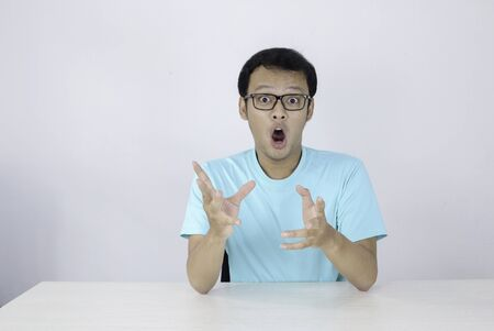 Wow and shocked face of Young Asian man with open hand gesture. Advertising model concept with blue shirt.
