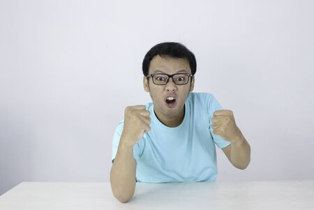 Angry and hate face of Young Asian man in blue shirt with angry hand gesture.
