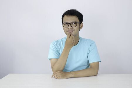 Young Asian man wear blue shirt and glasses with thinking and looking idea gesture in above empty space